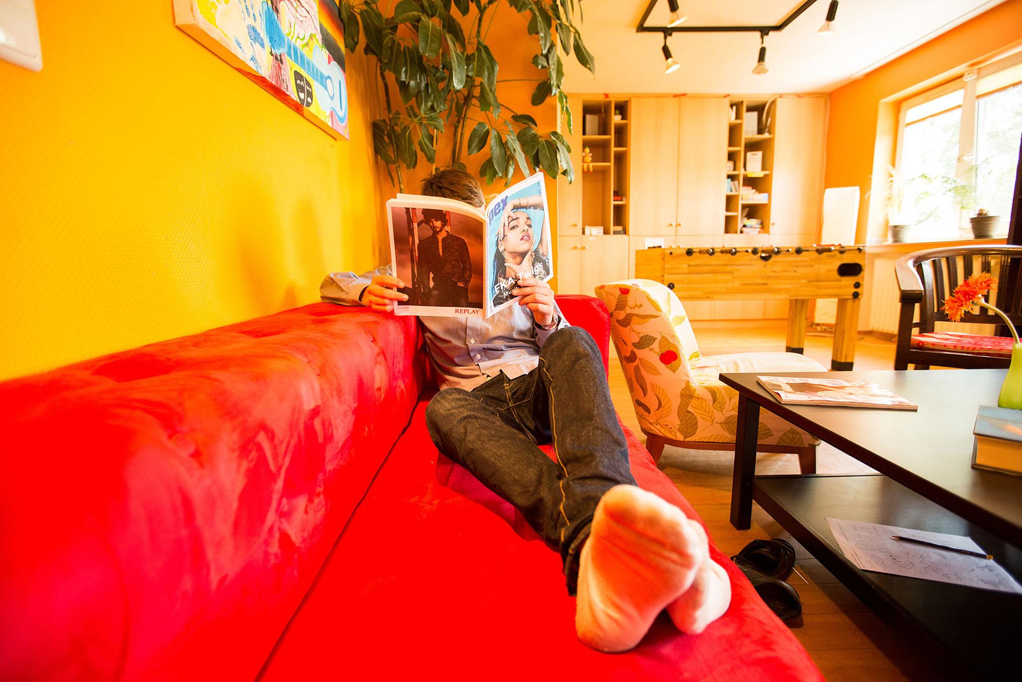Ein Junge liegt auf einer Couch und liest ein Magazin