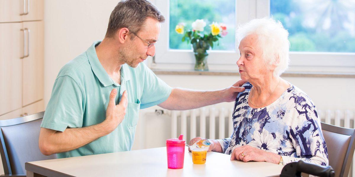 Patientin unterhält sich mit einem Angestellten