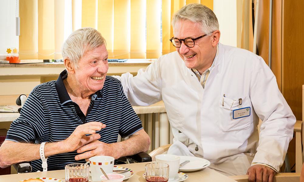 Dr. Heuer redet mit einem Patienten