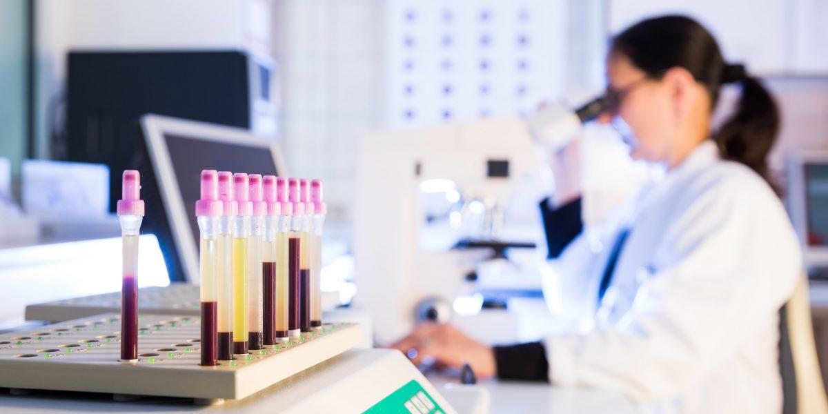 Ärztin macht Untersuchungen mithilfe eines Mikroskops